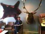 John in the car repair waiting room.  Yes, that's an elk head and a bear skin.